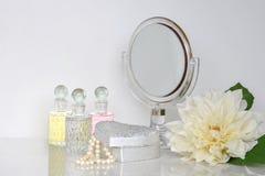 Liten spegel på en skänk som rundas med doftflaskor och casketen Fotografering för Bildbyråer