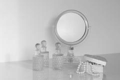 Liten spegel på en skänk som rundas med doftflaskor och casketen arkivbild