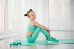 Liten sportig flickagymnast i sportswearen som gör övningar på ett mattt inomhus arkivbild