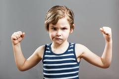 Liten Sportive tuff pojke som visar hans muskler Royaltyfri Bild