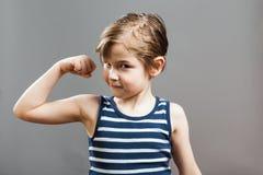 Liten Sportive tuff pojke som visar hans muskler Arkivfoton