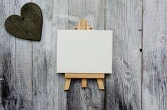 Liten staffli med en tom kanfas över vit och mörk trähjärta Gammal träbakgrund och stort kopieringsutrymme för ditt tecken fotografering för bildbyråer