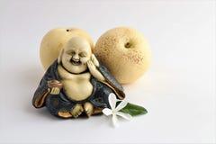 Liten staty av att skratta Buddha med päron royaltyfria bilder