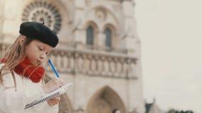 Liten stilfull flicka i basker som drar bilden i anteckningsbok nära Notre Dame i Paris, Frankrike som gör hennes hobby arkivfilmer