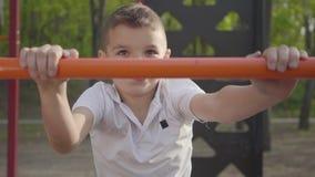 Liten stilig pojke för stående som klättrar barns moment på lekplatsnärbilden Aktiv livsstil, bekymmerslös barndom stock video