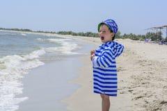 Liten stilig pojke på stranden i lyckliga randiga grimaser för en ämbetsdräkt Royaltyfri Foto