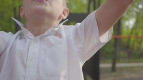 Liten stilig pojke som klättrar barns moment på lekplatsnärbilden Aktiv livsstil, bekymmerslös barndom som är förtjusande lager videofilmer