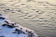 Liten ström som flödar på vintern under soluppgången Arkivfoton
