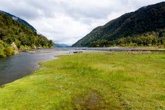 Liten ström som kommer från en glaciär som bildar en sjö mellan berg Grönt inklusive gräs och pir arkivfoto