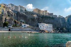 Liten strand under högväxta klippor på den Sorrento kusten, Italien, loppbegreppsdesign, utrymme för text arkivfoto