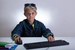 Liten student som spelar på datoren Royaltyfri Fotografi