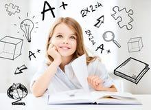Liten studentflicka som studerar på skolan Arkivbild