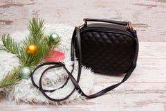 Liten svart kvinnlig handväska på en träbakgrund, granfilial med prydnader, stearinljus för begreppsframsida för skönhet blå ljus Royaltyfria Foton