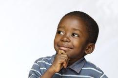 Liten svart pojke som tänker med handen på hans haka royaltyfri bild