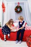 Liten syskongrupp som skrivar ett brev till jultomten mot som kroken för hang för dollar för bakgrundsbetebegrepp den gråa Arkivfoto