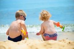 Liten syskongrupp som spelar med sand Fotografering för Bildbyråer