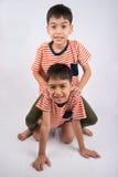 Liten syskonpojkebroder som ler att lägga ner samman med lycklig framsida Royaltyfria Bilder