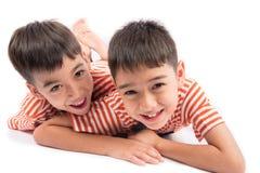 Liten syskonpojkebroder som ler att lägga ner samman med lycklig framsida Arkivbild