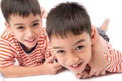 Liten syskonpojkebroder som ler att lägga ner samman med lycklig framsida Royaltyfria Foton