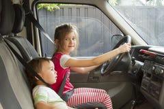 Liten syster och broder som kör en bil Arkivfoton