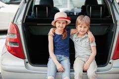 Liten syster och broder som sitter i stammen av en bil med resv?skor royaltyfri bild
