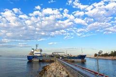 Liten tankfartyg under päfyllning på en pir Royaltyfri Fotografi