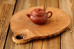 Liten tekanna yixing för röd lera på träbräde Arkivfoto