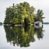 Liten träd-fylld kanadensisk ö med sjöboden Arkivfoto
