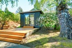 Liten trädgårds- studio i ett separat rum med fönsterväggar. arkivfoto