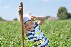 Liten trädgårdsmästare med skyffelanseende i potatisfält Arkivfoton
