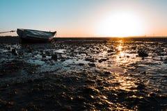 Liten träfiskebåt på solnedgången på stranden Fotografering för Bildbyråer