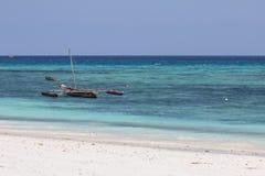 Liten träfiskebåt vid den vita sandstranden i Zanzibar arkivfoto