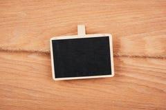 Liten träinramad svart tavla som hänger på träbakgrund svart tavla med stället för din text Arkivbild