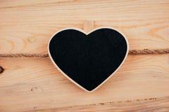 Liten träinramad svart tavla som hänger på träbakgrund svart tavla med stället för din text kopiera avstånd Royaltyfria Foton
