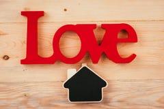 Liten träinramad svart tavla som hänger på träbakgrund svart tavla med stället för din text Träbokstav för röd förälskelse Arkivfoton