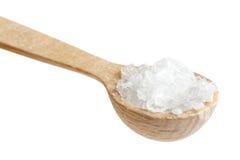 Liten träsked av grovt salt på vit Arkivbilder