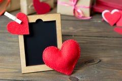 Liten trästaffli, röd hjärta som göras av filt Fotografering för Bildbyråer
