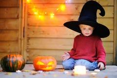 Liten trollkarl som spelar med halloween pumpor Arkivfoto
