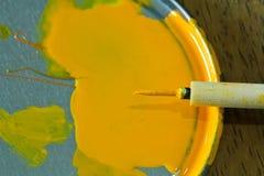 Liten tunn målarpensel med målarfärg på en palett Royaltyfri Fotografi
