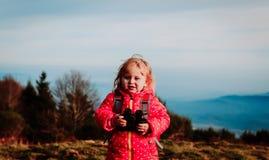 Liten turist med kikarelopp i berg royaltyfri bild