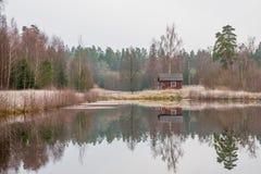 Liten typisk stuga vid en sjö Royaltyfria Bilder