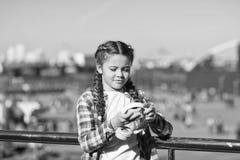 Liten unge för flicka att rymma hopfällbar hörlurar, medan gå utomhus Grej för modern musik Fördelar av hopfällbar hörlurar arkivbild