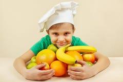 Liten unge i kockhatt med frukter på tabellen Arkivfoto