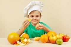 Liten unge i kockhatten som skalar den nya apelsinen på tabellen med frukter Arkivbilder