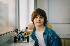 liten unge med den diy roboten på stammen royaltyfria foton