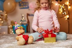 Liten unge med leksakbjörnen i barnkammare royaltyfria foton