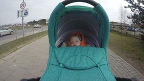 Liten unge med ritt för rompersömnbarnvagn över stadsgatan 4K lager videofilmer