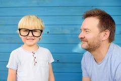 Liten unge med stora exponeringsglas och hans fader på blå träbackgraund Klyftiga childs royaltyfri foto