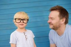 Liten unge med stora exponeringsglas och hans fader på blå träbackgraund Klyftiga childs fotografering för bildbyråer