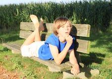 Liten unge - pojke på en bänk Royaltyfria Foton